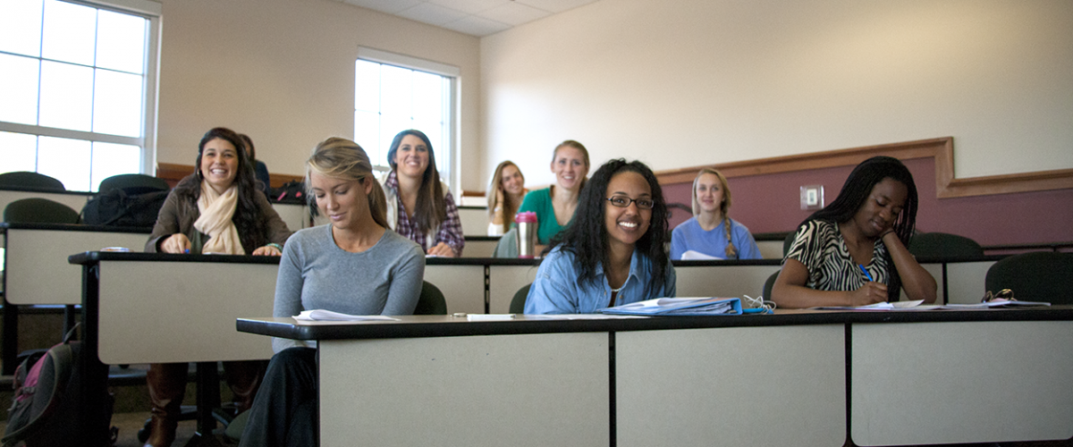 Female students in Daleah Goodwin's Women's Studies class smile in desks